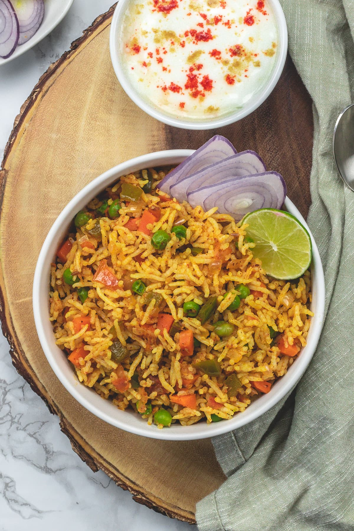 A bowl of tawa pulao garnished with onion slices, lime wedge and yogurt served on side.