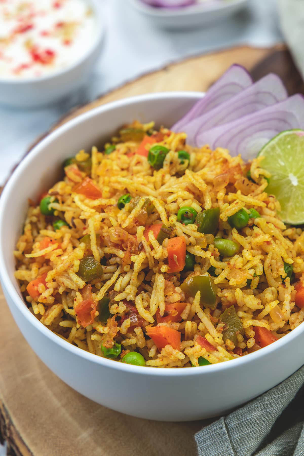 Tawa pulao in a bowl garnished with onion rings and lime wedge.
