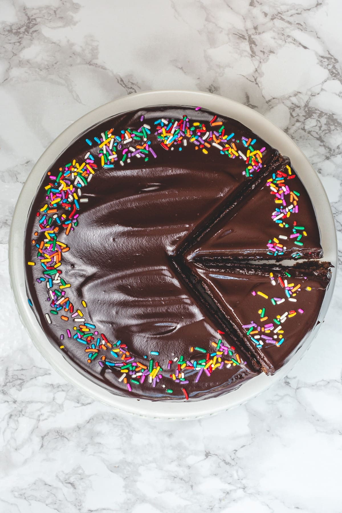 Top view of eggless chocolate cake with two slices on a cake stand.