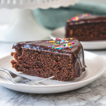 a slice of eggless chocolate cake in a plate with fork.