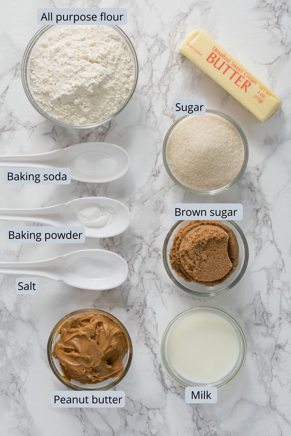 Ingredients used for eggless peanut butter cookies in individual bowls and spoons.