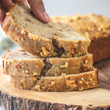 A stack of banana bread slices on a wooden board and taking away one slice.