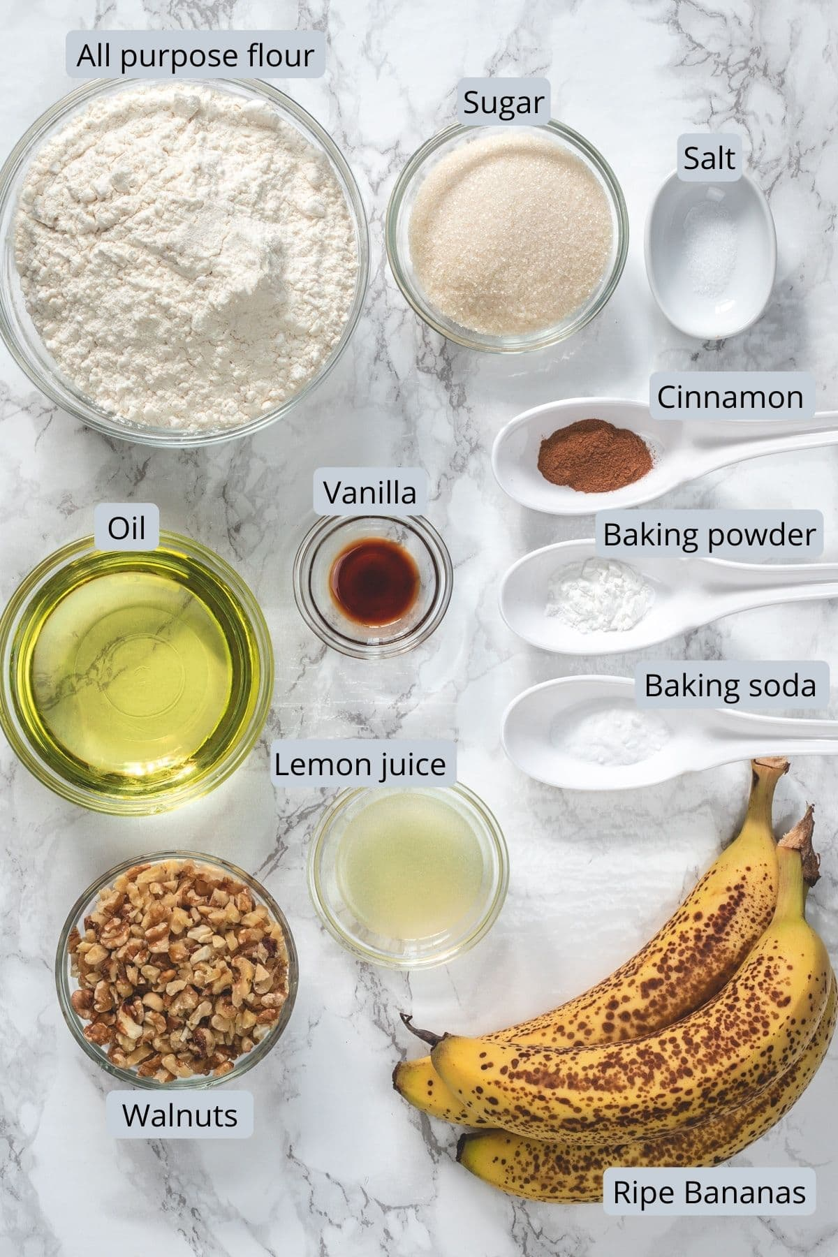Eggless banana bread ingredients removed in individual bowls and spoons.
